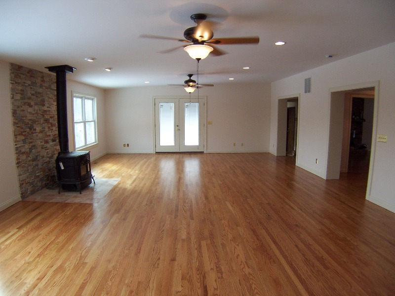 Hardwood Flooring & Free Standing Stove With Stacked Stone Backdrop