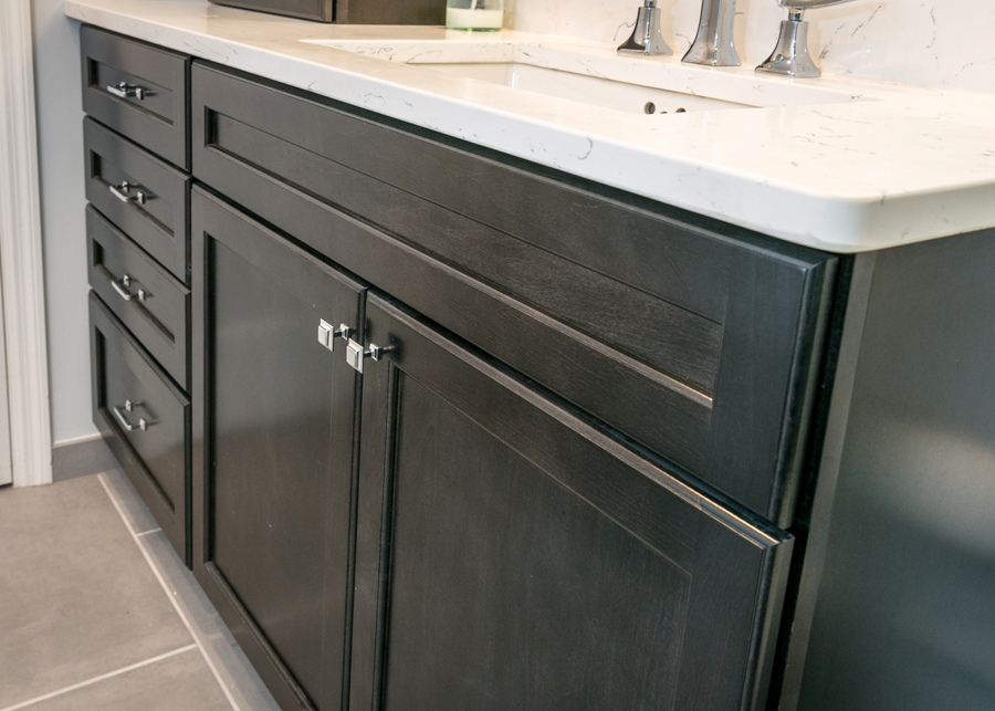 Vanity cabinets stained black in a modern bathroom design.