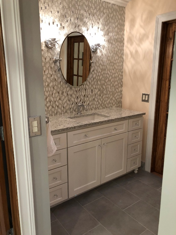 Full mosaic tiled backsplash with light sconces and oval mirror.