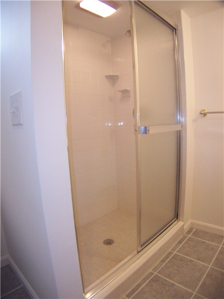 White 4 by 4 tiles and a fiberglass shower pan offer cost savings to a bathroom remodel.