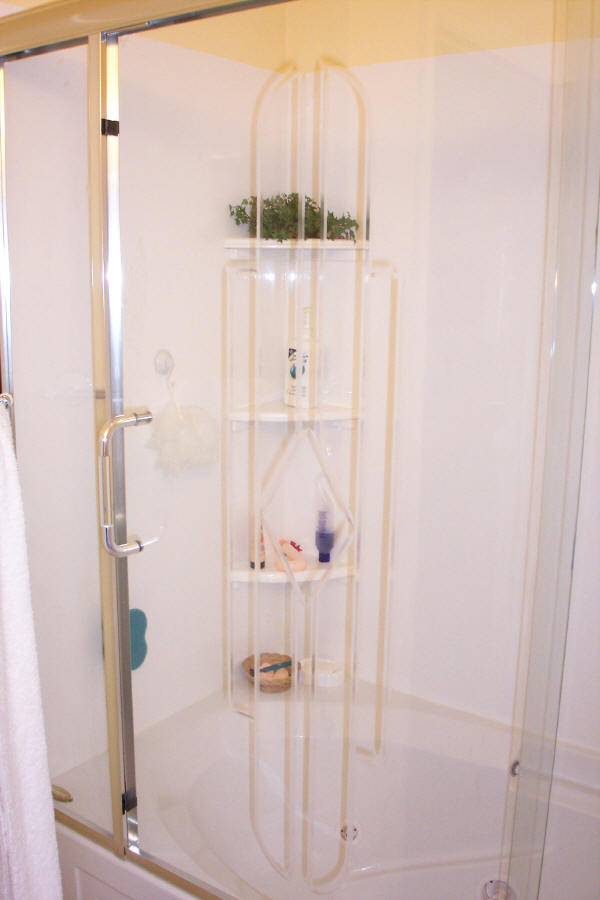 A framed and hinged shower combined with a fiberglass tub surround offer cost savings to a bathroom remodel.